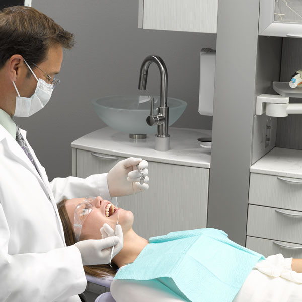 Dentist attending to patient in A-dec dental equipment operatory