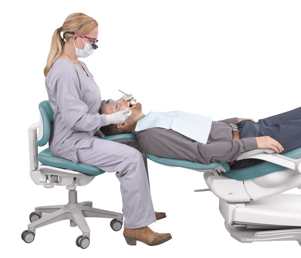 Dentist in ergonomic position with A-dec dental stool and dental chair